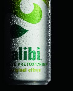 Closeup shot of Alibi soft drink with condensation on can against black background - Food and drink photography