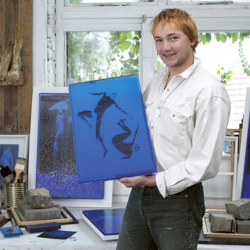 Young male artist showing artwork in his studio - People photography