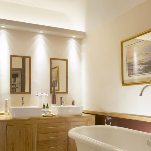Modern white bathroom in hotel suite with double sinks electrical photography