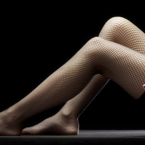 Female legs wearing fishnet holdups with little pink bow - Product photography