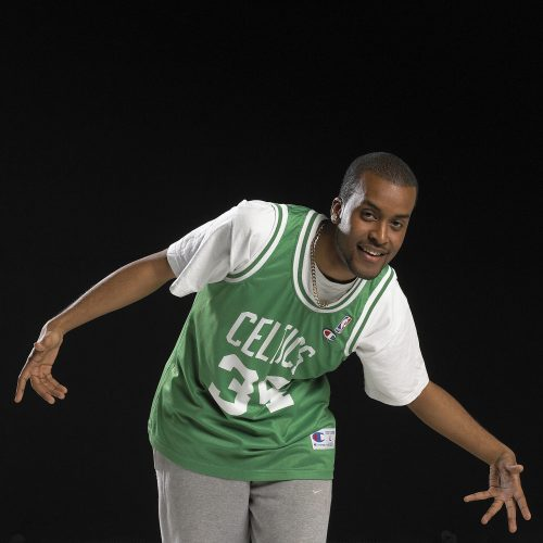 Young black male, striking a pose, wearing green white basketball tshirt against black background - People photography