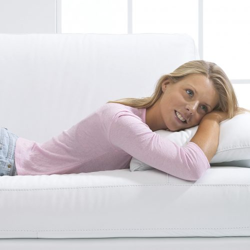 Young blonde lady laying on white sofa wearing pink tshirt and denim shorts - People photography