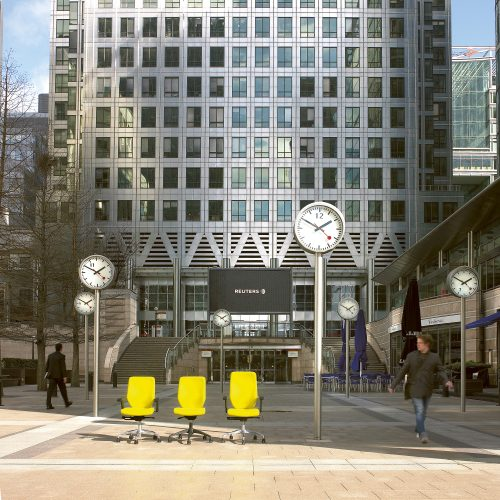 Yellow office chairs in line at Canary wharf with clocks - Exterior/Location photography