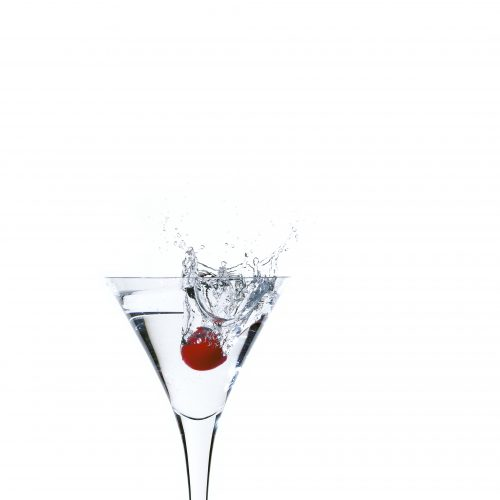 Cherry splashing into a martini glass on white background concept photography