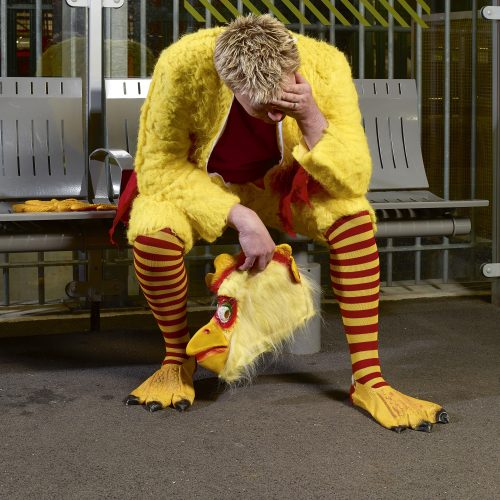 Man wearing chicken fancy dress costume, sitting on train station platform with head in hands - People photography