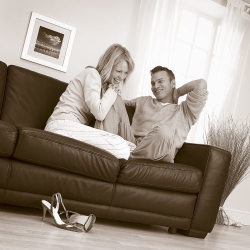 Couple sitting together on dark leather sofa in lounge environment - People photography