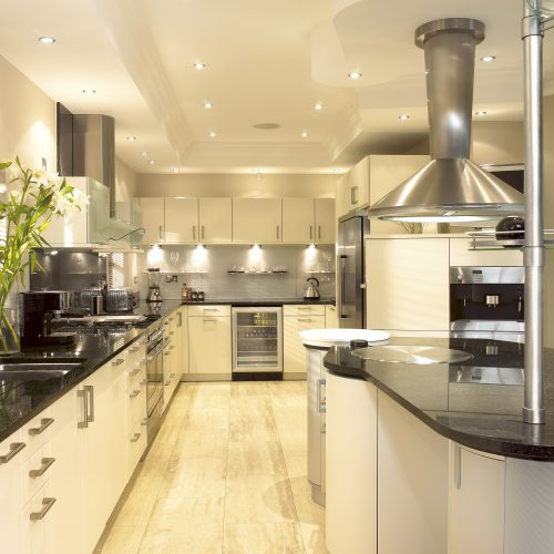 Large modern cream kitchen with Chrome and black worktops and downlights