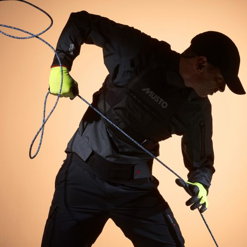 Sihouette of man pulling on rope wearing Musto yellow dipped gloves - product photography
