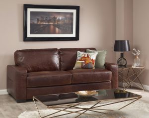 Chocolate brown leather two piece suite in studio roomset with coffee table a framed picture on wall - Furniture photography