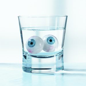 Drinking glass and water with two fake glass eyes on white background with slight shadow - concept photography