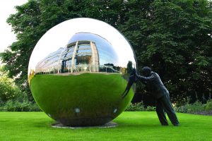 Statue of man pushing large chrome ball reflections of building sky grass concept photography