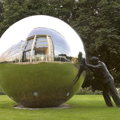 Statue of man pushing large chrome ball reflections of building sky grass - Exterior photography