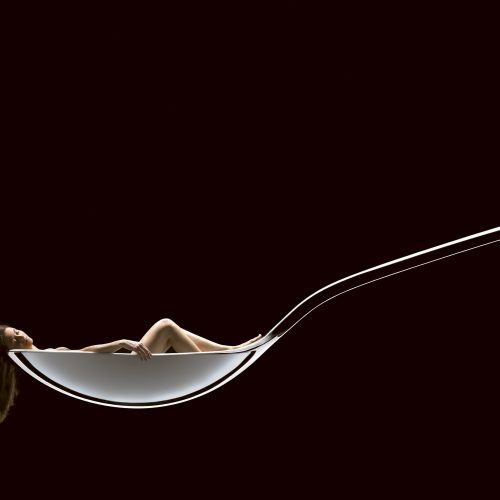 Lady with long hair laying in spoon concept photography