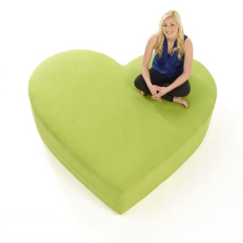 LV Green heart sofa with blonde girl sitting in top corner, studio shot on white background - People photography