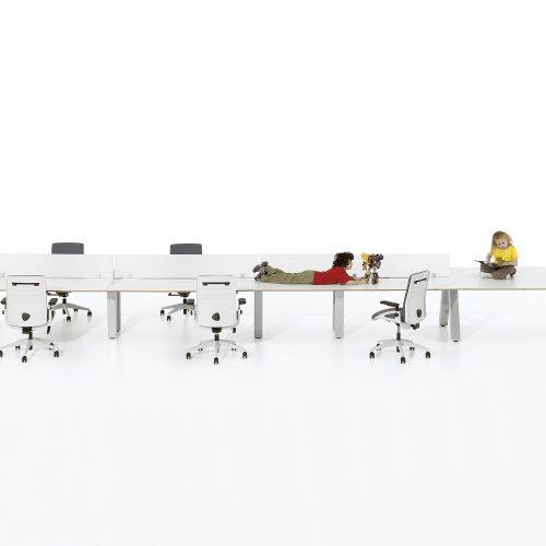 Long white desking unit with small children sitting on desk, white background - Furniture photography