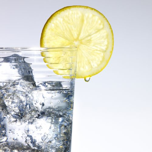 Lemon slice on side of glass filled with fizzy tonic and ice - Food and drink photography
