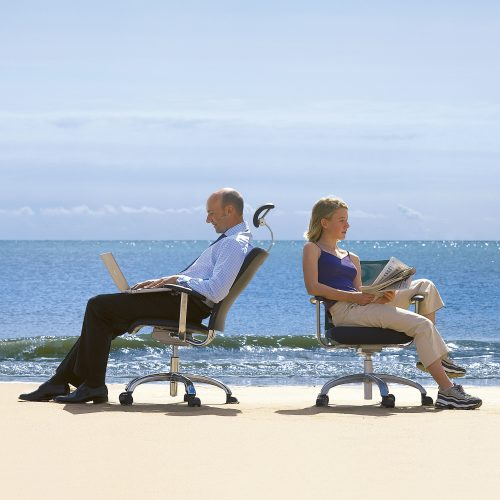 Two people sitting back to back on office chairs at Beach - Furniture photography
