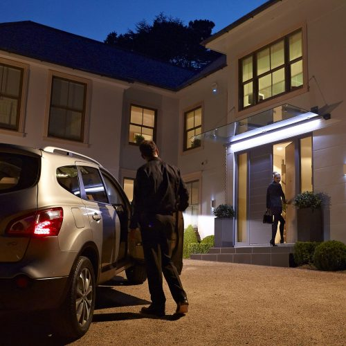 Night shot of young couple returning to large modern house with car - Exterior photography
