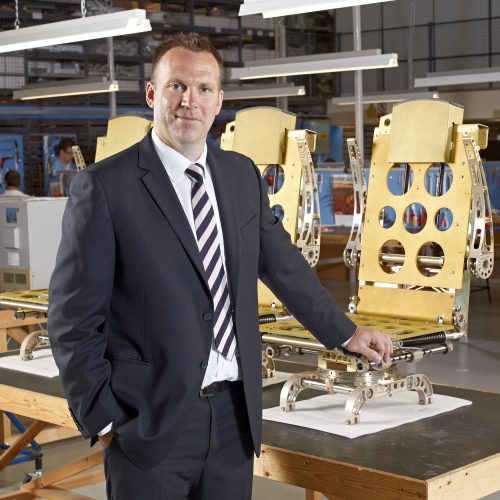 Man wearing dark suit standing in front of Airplane chairs manufacturing - People photography