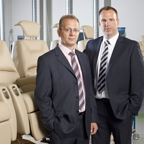 Two males standing in front of cream leather airplane seats - People photography