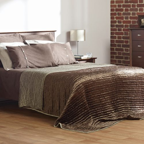 Taupe bedding in bedroom set with brick wall and window - Furniture photography