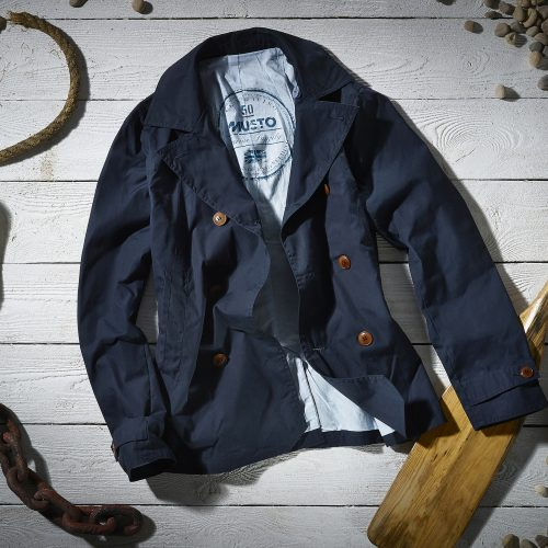 Moody Musto shot of navy sailing jacket on wooden deck with oars, rope and rocks - product photography
