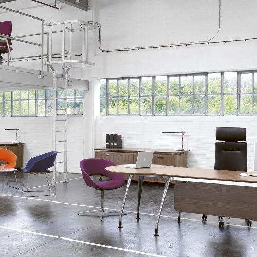 Industrial office space with funky colour chairs and dark wooden desk - Furniture photography