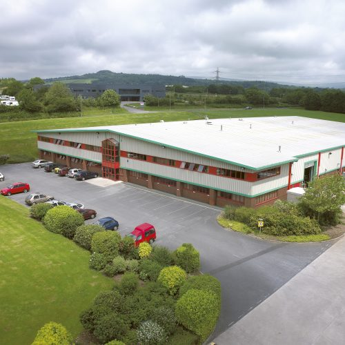 Aerial shot of large warehouse set in countryside - Exterior photography