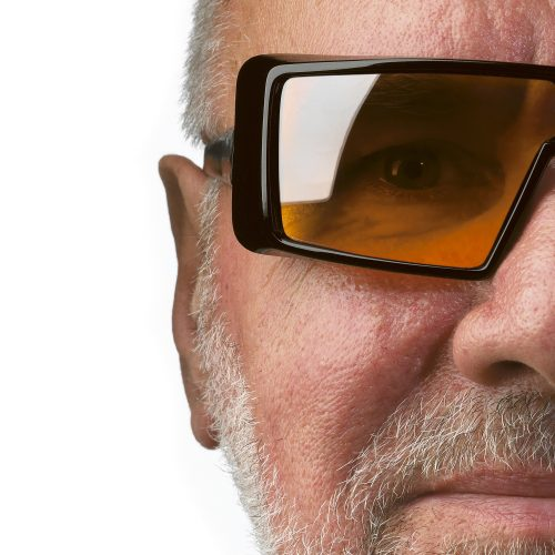 Older male with grey hair & beard wearing large square sunglasses on white background - People photography