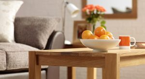 Closeup of corner of coffee table with bowl of oranges and sofa & light in background - Furniture photography