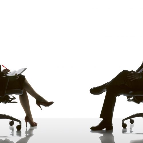 Silhouette of two people sitting on office chairs against white background - Furniture photography
