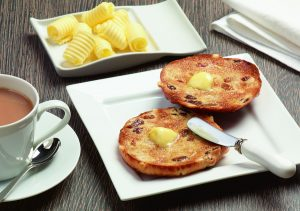 Square plates with toasted teacake curled butter cup of tea and small white handled knife - Food and Drink Photography