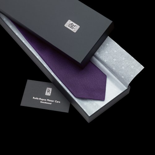 Rolls Royce purple tie in presentation box on black background - product photography
