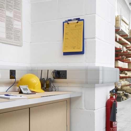 Industrial warehouse with MK Trunking, computer & sockets in foreground, forklift truck in background - Product photography