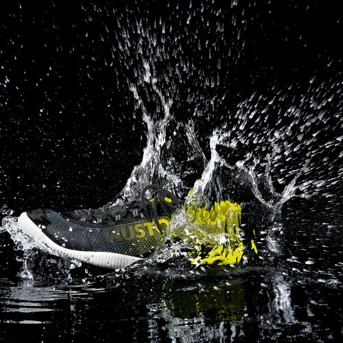 Musto training shoe splashing in water against black background - product photography