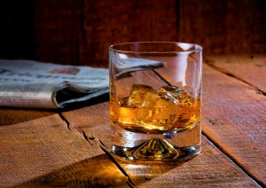 Tumbler of whisky and ice on wooden background with newspaper - Food and drink photography