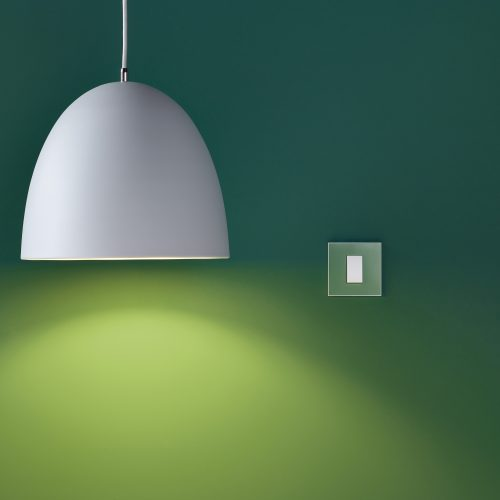 Green wall with large white lampshade and switch electrical photography