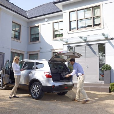 Young professional couple loading car for holiday in front of large white modern house - Exterior photography
