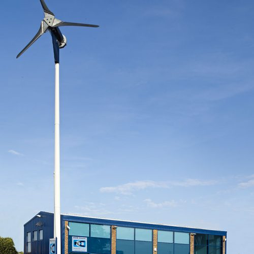 Office Building with large Wind turbine outside, blue sky - Exterior/Location photography
