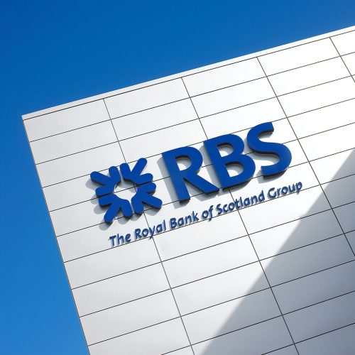 Close up of RBS logo on building, blue sky - Exterior/Location photography